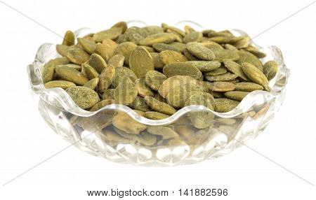A small glass bowl filled with organic dry roasted pumpkin seeds isolated on a white background.