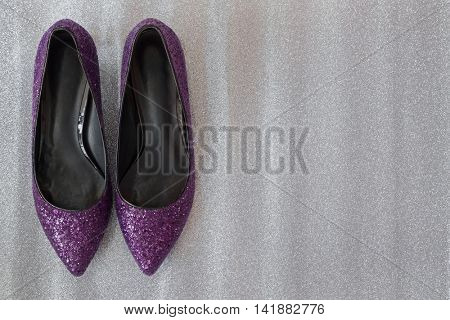 Top view of new pair of sparkling stylish purple magenta high heels, beautiful shoes with glitters for ladies on glittery silver background