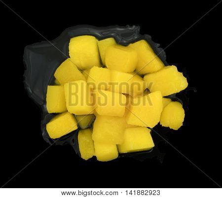 A portion of diced mangoes in light syrup on a black background.