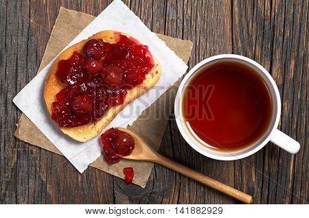 Cup of hot tea and cherry jam with toasted bread in plate on rustic wooden table top view