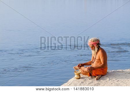 ALLAHABAD, INDIA - FEB 14 - A Hindu pilgrim sits in meditation on the banks of the holy river during the festival of Kumbha Mela on February 14th 2013 at Allahabad, India.
