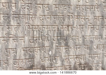 An ancient Buddhist text in Sanskrit etched into a stone tablet. poster