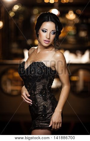 Young brunette lady posing in a glamorous interior