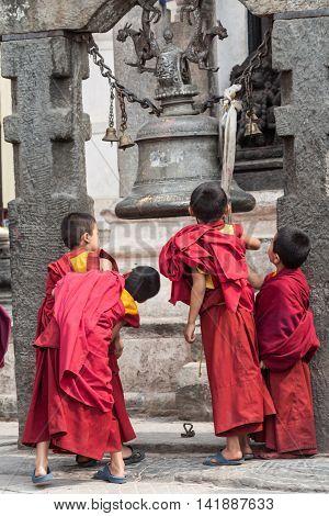 NEPAL, Swayambhunath - 4th May 2014 - Young Buddhist children looking in a shop window in Swayambhunath, Nepal.