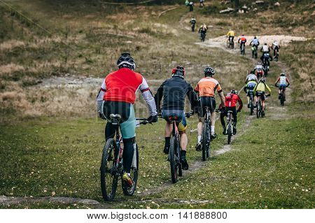 group of cyclists mountainbikers riding on a mountain for each other. extreme sports cross-country