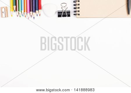 Top view of white tabletop with empty spiral notepad colorful pencils sharpener peg and other stationery items. Close up Mock up