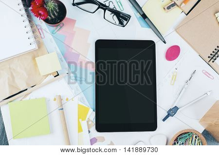 Blank tablet on messy office desktop with business report cactus glasses and various stationery items. Top view Close up Mock up