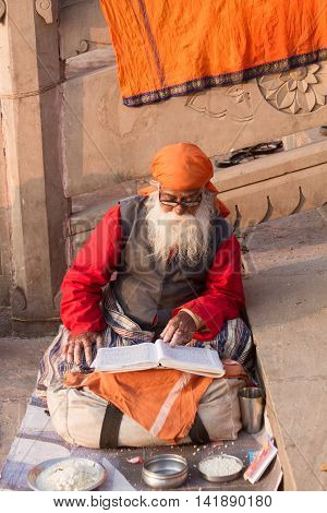 VARANASI, INDIA - FEB 18 - An old sadhu in Varanasi reading holy scripture on February 18th 2013