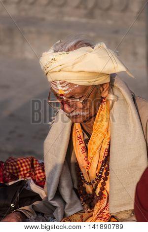VARANASI, INDIA - FEB 18 - An old pandit sits and reads a Hindu holy book in Varanasi on February 18th 2013