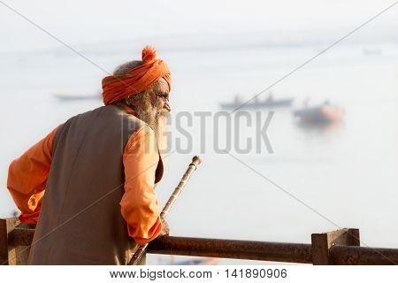 VARANASI, INDIA - FEB 18 - An old Hindu sadhu look out at the River Ganges in Varanasi on February 18th 2013