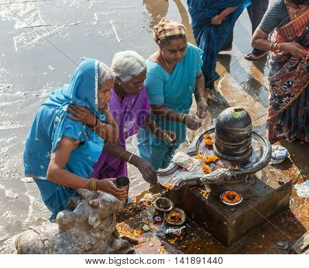 VARANASI, INDIA - FEB 18 - A group of ladies worshiping a Shiva linga in Varanasi on February 18th 2013