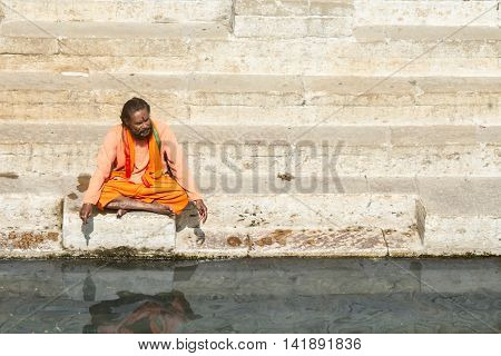 VARANASI, INDIA - FEB 18 - A sadhu sits on the ghats overlooking he Ganges river in Varanasi on February 18th 2013