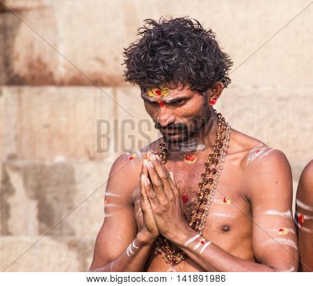 VARANASI, INDIA - FEB 18 -  A Young Hindu man offers respects to the holy river Ganges