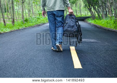 Hitchhiking Tourism Concept. Travel Hitchhiker Man With Backpack Walking On The Road Passes Through