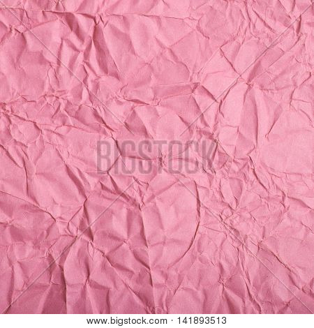 Close-up fragment of a pink crumpled paper texture as a backdrop composition