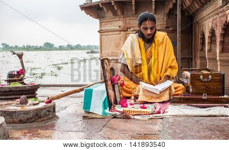 VRINDAVAN, INDIA - OCT 15 - A young sadhu sitting on the ghats on the banks of the Yamuna in Vrindavan reciting from the Hindu scriptures on October 15th 2009