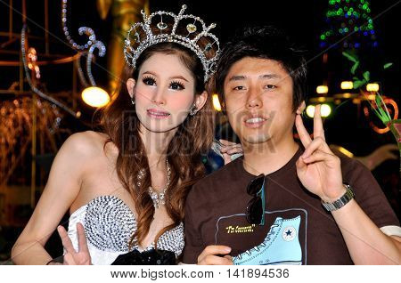 Pattaya Thailand - January 5 2010: Chinese tourist poses with a beautiful ladyboy
