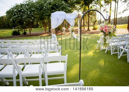 chairs and arbor with hanging flowers for wedding, focus on flowers in jar