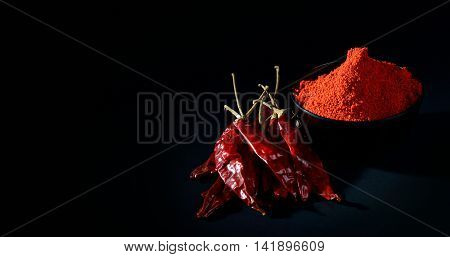 chilly powder in black bowl with red chilly, dried chillies on black background
