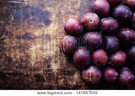 Fresh plums on a dark wood background. Top view image. Ripe Plums Texture