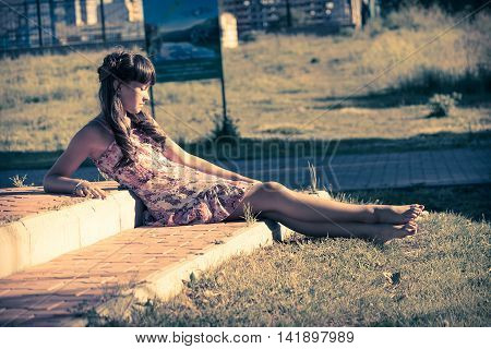Beautiful teenage girl in pink dress with long hair in a green summer park special tone horizontal view