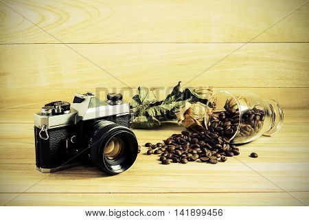 Camera Film And Coffee Bean On Wooden Table.