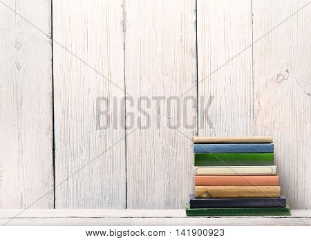 Old Books on Wood Shelf Spine Cover over White Wooden Wall Background