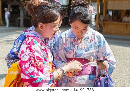 KAWAGOE JAPAN - 20 JULY 2016 - Japanese women in traditional yugata read their fortune paper at Hikawa Shrine in Kawagoe Japan on July 20 2016.