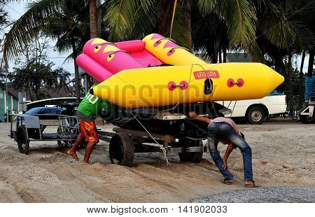 Bang Saen Thailalnd - January 8 2014: Two Thai workers hauling a banana boat and speedboat across the sand at Bang Saen beach at the end of the day