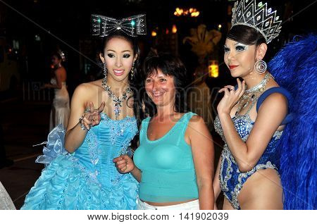 Pattaya Thailand - January 3 2010: Tourist poses with two of the ladyboy performers after a show at the famed Alcazar Theatre