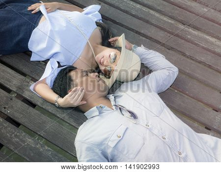 Beautiful woman and handsome man of romantic couple are sprawl on wooden bridge with color tone effect