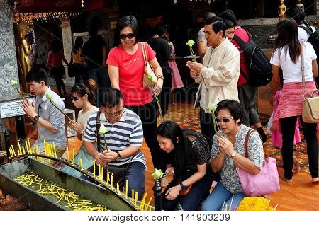 Chiang Mai Thailand - December26 2012: Devout Thais holding Lotus flowers praying in front of a candle bower at Wat Doi Suthep