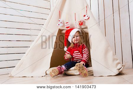 pretty little girl in red santa hat sitting near wigwam with toy-ball in hand