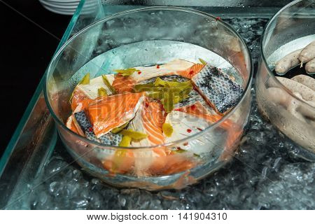 Salmon pieces in a glass bowl cooling on ice ready for grilling top view
