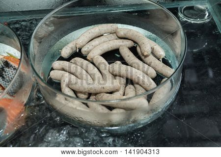 Delicious sausages in a glass bowl coolant stored on ice ready for grilling top view