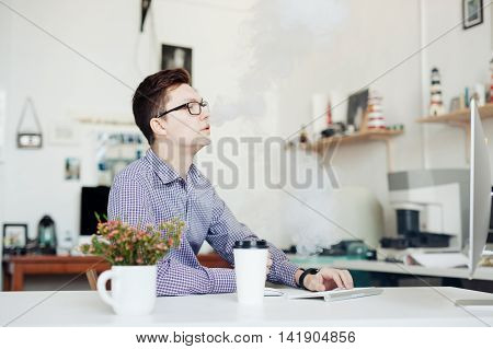 man in office smoking with electronic cigarette