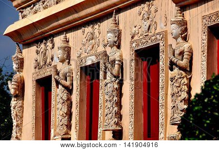 Chiang Mai Thailand - January 3 2013: Thai Khong figures with hands clasped in prayer decorate the base of the  Repository Library at Wat Phra Singh *