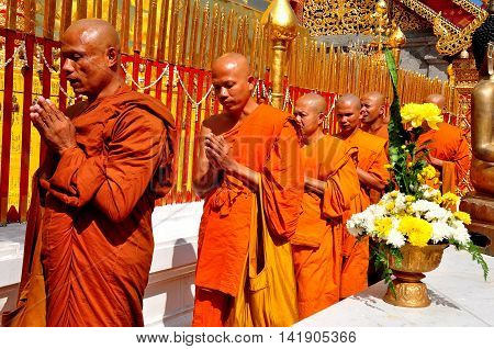 Chiang Mai. Thailand: - December 26 2012: Monks with their hands clasped in prayer walking in procession around the  golden Chedi at Wat Doi Suthep *