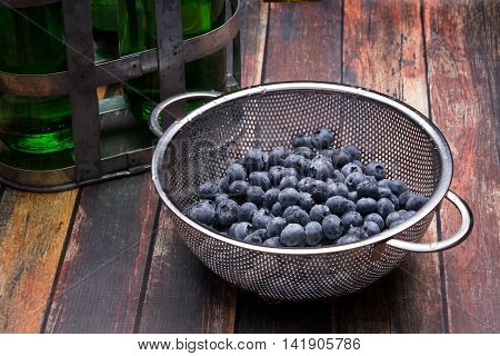Fresh blueberries in stainless steel colander on a wood surface