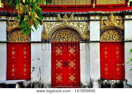 Chiang Mai Thailand - December 18 2012: Three red doorways with gilded carved dragon tails of and mythical figures adorn a temple pavilion at Wat Mulan