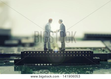 two mini businessman shake hand on stand on mainboard for make a deal on effect light fare - can use to display or montage on products