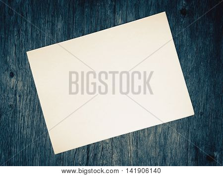 Blank old white paper on blurred of blue wooden background