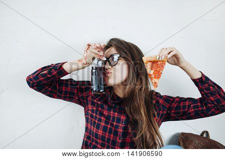 closeup of young girl eating pizza and drinking cola.
