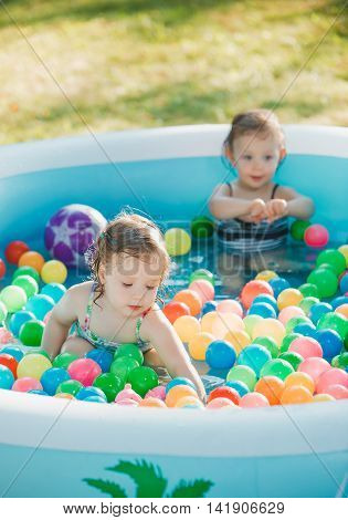 The two Two-year old little baby girls playing with toys in inflatable pool in the summer sunny day