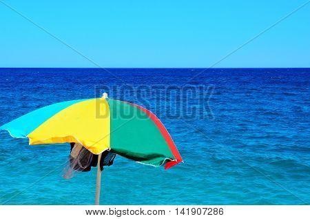colorful umbrella in the emerald sea of Bergeggi Savona Italy
