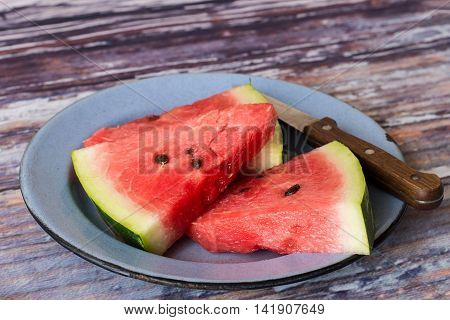 Pieces of juicy ripe watermelon and  knife in an old metal bowl on a wooden table.