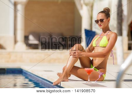 Young beautiful slim brunette woman with elegant hairstyle,dark sun glasses,wearing earrings,smooth dark tan,wearing a bikini is yellow,sitting by the pool with a glass of rose alfresco drink in the summer