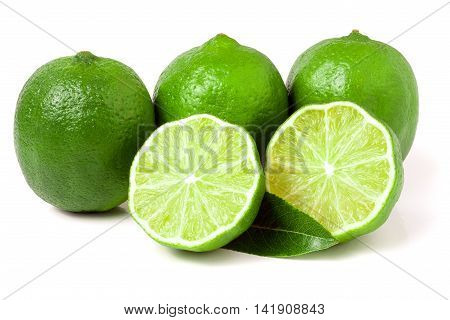three limes with halves and leaf isolated on white background.