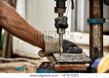 Drill press drilling a steel plate, drilling