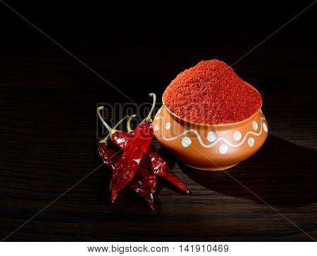 chilly powder in clay pot with red chilly, dried chillies on wooden background